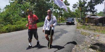 Ibrahim Rusli (kanan) berjalan kaki dengan membawa bendera Merah Putih, ditemani Kepala Dispora Kota Tarakan Agus Sutanto. (foto: jendelakaltara.co)
