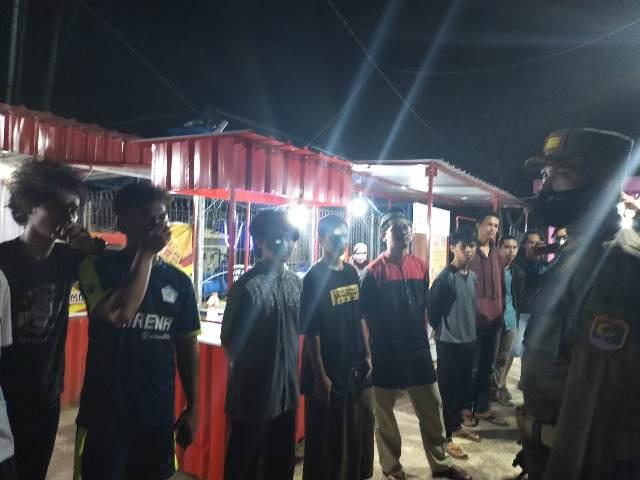 Sejumlah pemuda yang tidak menggunakan masker dikumpulkan untuk diberi sanksi menyanyikan lagu Indonesia Raya. (foto: jendelakaltara.co)