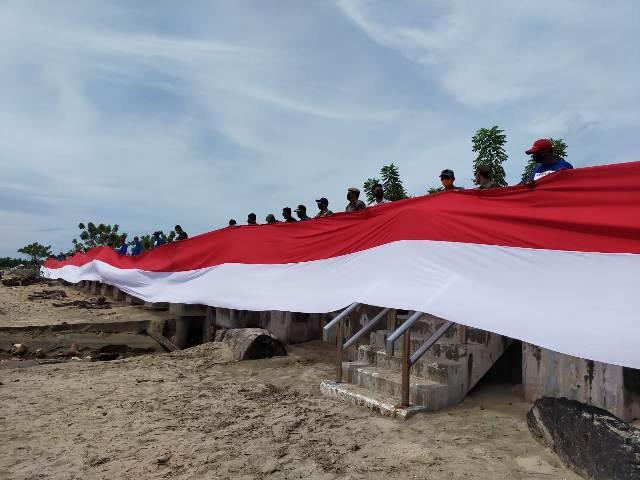 Peserta membentangkan bendara Merah Putih disela kegiatan bersih-bersih di Pantai Amal Lama dalam rangka memperingati Hari Sumpah Pemuda ke-92 yang dipusatkan di Tarakan, Rabu (28/10/2020). (foto: jendelakaltara.co)