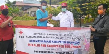 Wakil Ketua Penanggulangan Bencana PMI Provinsi Kaltara H. Harianto  menyerahkan bantuan kepada warga terdampak. (foto: Dok PMI Provinsi Kaltara)