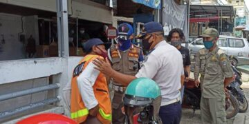 Petugas menjumpai salah satu juru parkir. (foto: istimewa)