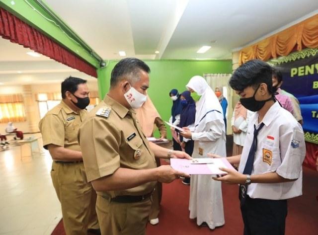 Wali Kota Tarakan dr. H. Khairul M.Kes menyerahkan beasiswa prestasi bagi perwakilan para pelajar tingkat SD/MI/SMP/MTs di Kota Tarakan, 3 Agustus 2020. (foto: Dok Humas Setda Tarakan)
