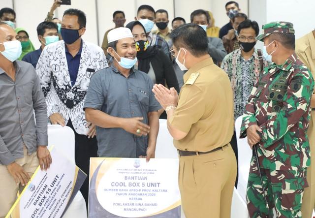 Gubernur Kaltara, Dr. H. Irianto Lambrie saat menyerahkan secara simbolis bantuan pengolahan dan pemasaran hasil perikanan, Senin (7/12). (Foto: Humas Provinsi Kaltara)