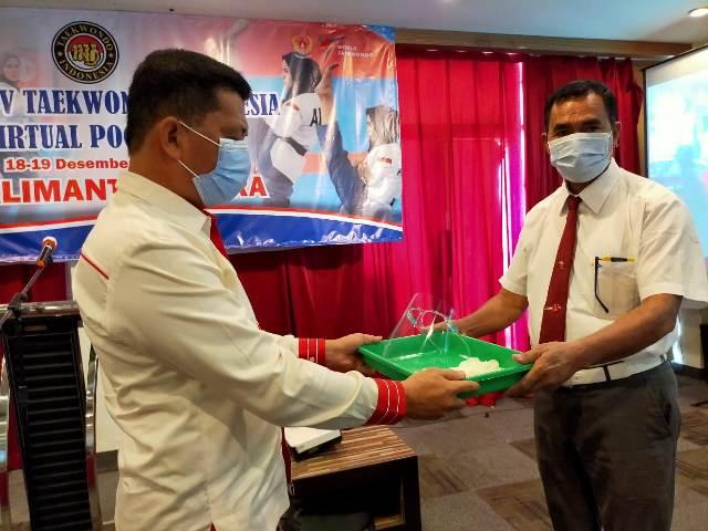 Ketua Pengprov TI Kaltara Muhammad Nasir (kiri) memberikan Alat Pelindung Diri (APD) berupa hazmat dan masker kepada perwakilan wasit. (foto: jendelakaltara.co)