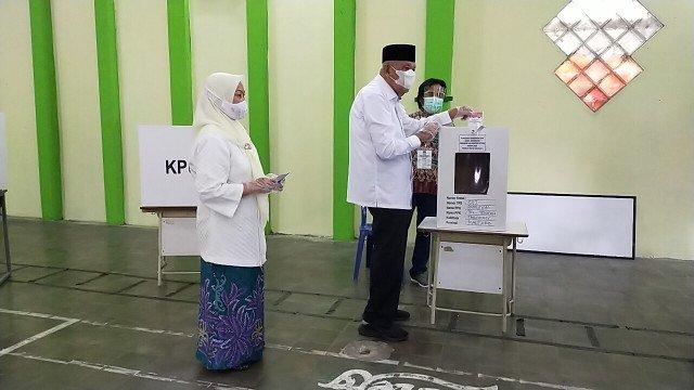 Calon Gubernur Nomor Urut 1 Udin Hianggio bersama istri  Zulaeha Ma'aruf menyalurkan hak pilihnya di TPS 12 Kelurahan Pamusian, Kecamatan Tarakan Tengah, Rabu (9/12/2020). (foto: jendelakaltara.co).