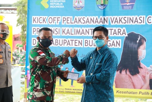 Gubernur Kaltara, Dr. H. Irianto Lambrie (kanan) menyerahkan dokumen kartu vaksin, kepada Danrem 092/Maharajalila di Puskesmas Tanjung Selor, Kamis (14/1). (Humas Provinsi Kaltara)