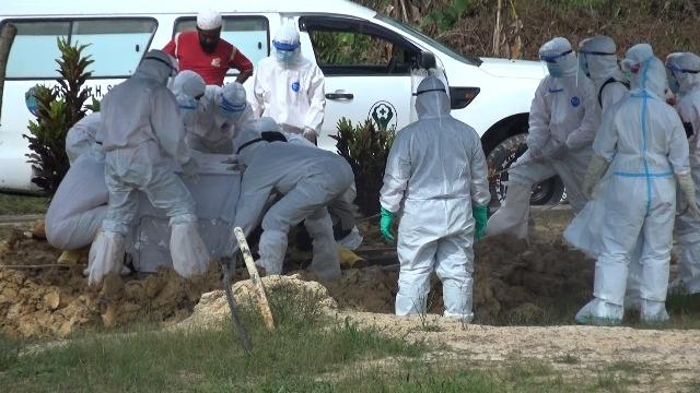 Petugas memakamkan jenazah pasien Covid-19. (foto: AG/jendelakaltara.co)
