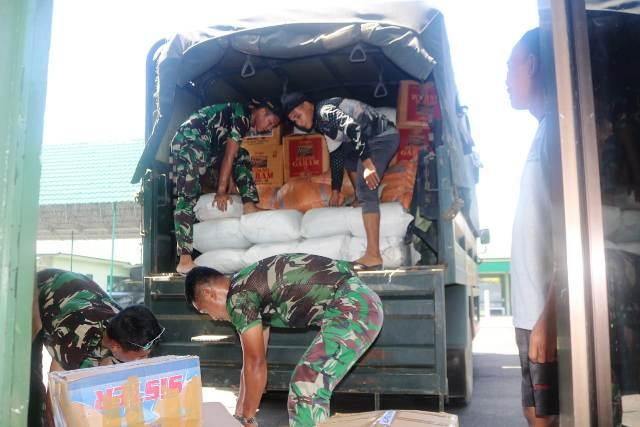Prajurit Kodim 0907/Trk menaikkan bantuan kebutuhan pokok ke truk. (foto: Kodim 0907/Trk)