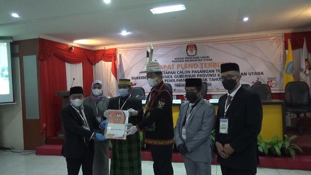 Ketua KPU Kaltara Suryanata Al Islami menyerahkan berita acara penetapan kepada Gubernur dan Wakil Gubernur Kaltara terpilih Zainal Arifin Paliwang dan Yansen Tipa Padan. (foto: jendelakaltara.co)