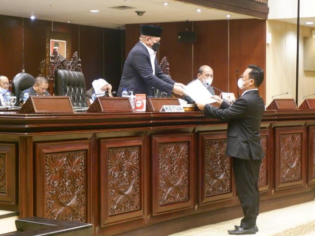 Wakil Ketua Komite II DPD RI Hasan Basri (kanan) menyerahkan laporan Pelaksanaan Tugas Komite II DPD RI kepada pimpinan Sidang Paripurna ke-8 DPD RI, Kamis (11/2/2021). (foto: Tim Hasan Basri)