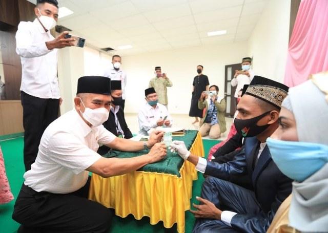 Wali Kota Tarakan dr. H. Khairul M.Kes menyerahkan kartu nikah kepada pasangan pengantin. (foto: Humas Setda Tarakan)