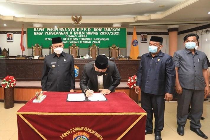 Ketua DPRD Tarakan Al Rhazali menandatangani berita acara pengesahan Raperda Zakat menjadi Perda Zakat di ruang rapat utama gedung DPRD Tarakan, Selasa (23/2/2021). (foto: Humas Setda Tarakan)