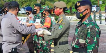 Kapolres Nunukan AKBP Syaiful Anwar S.IK  menyerahkan simbolis bantuan masker dan sembako kepada perwakilan satuan tugas baik Polri, TNI dan Satpol PP, Senin (22/2/2021). (foto: Humas Polres Nunukan)