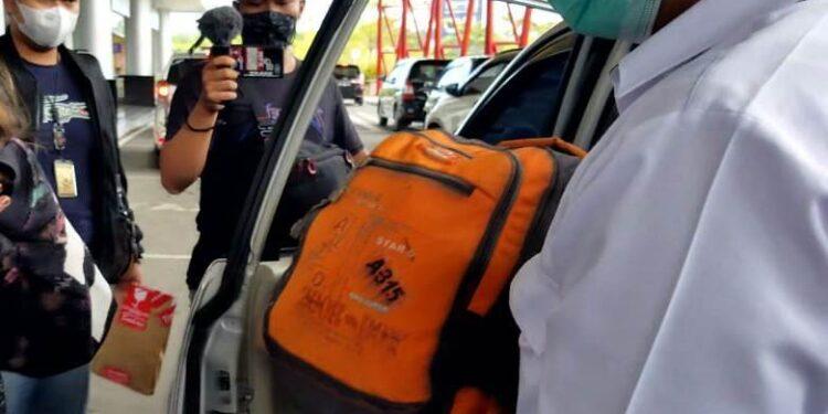 Polisi menjemput tersangka yang tiba di bandara Juwata Tarakan, Rabu (24/2/2021). (foto: Istimewa)