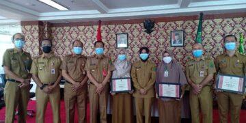Bupati Nunukan Hj. Asmin Laura Hafid SE, MM bersama kepala puskesmas peraih penghargaan SPM. (foto: Humas Setda Nunukan).