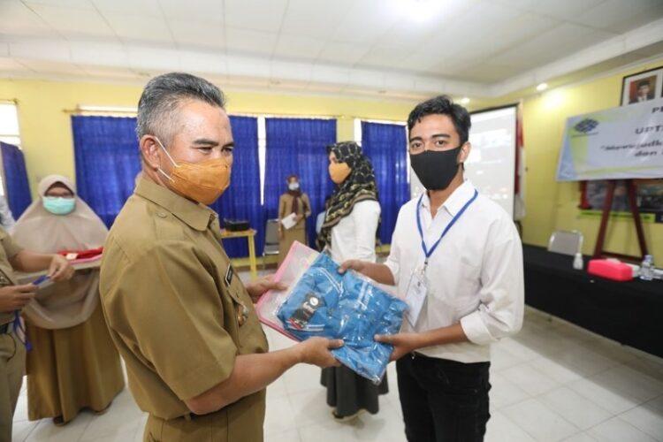 Wali Kota Tarakan dr. H. Khairul M.Kes (kiri) menyerahkan seragam kepada peserta. (foto: Humas Setda Tarakan)