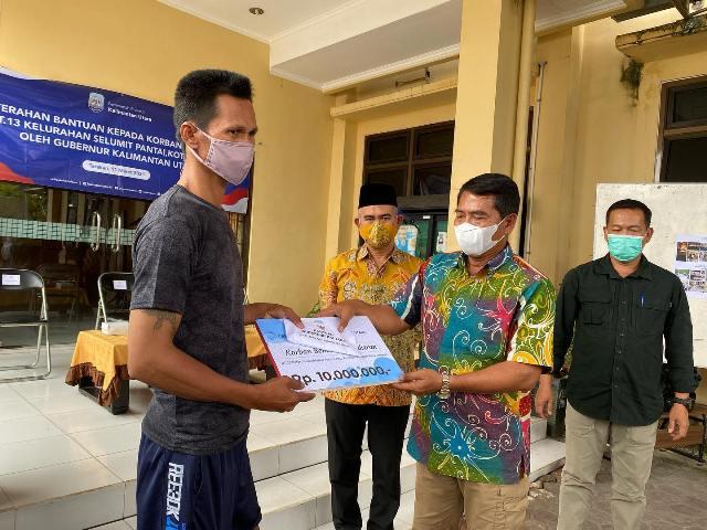Gubernur Kaltara H. Zainal Arifin Paliwang menyerahkan bantuan kepada warga terdampak kebakaran di kelurahan Selumit Pantai, Kamis (11/3/2021). (foto: Humas Setda Tarakan)