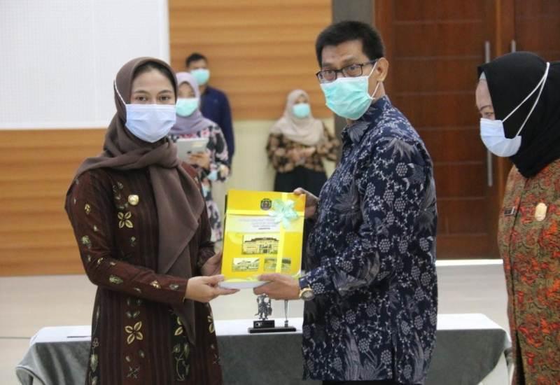 Bupati Nunukan Hj. Asmin Laura Hafid (kiri) menyerahkan LPKD kepada Kepala Sub Auditorat BPK Kaltara Joni Rindra Putra, Selasa (9/3/2021). (foto: BPK Perwakilan Kaltara)
