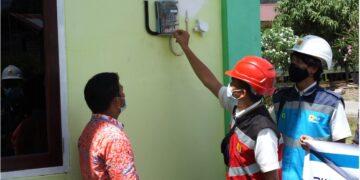 Petugas PLN mengecek KWh meter di salah satu rumah warga. (foto: PLN Kaltara)