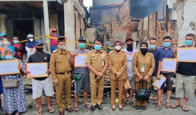 Gubernur Kaltara Zainal A. Paliwang didampingi Bupati Nunukan Hj. Asmin Laura Hafid menyerahkan bantuan bagi korban kebakaran di Pasar Lama Nunukan, Selasa (23/3/2021). (foto: Diskominfo Kaltara)