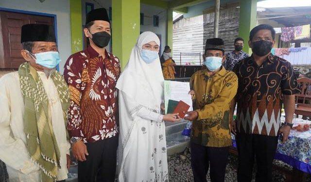 Bupati Nunukan Hj. Asmin Laura Hafid menyerahkan simbolis buku nikah kepada pasangan suami istri yang telah mengikuti sidang isbat. (foto: Humas Setda Nunukan)