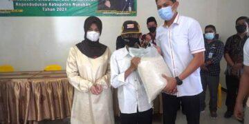Bupati Nunukan Hj. Asmin Laura Hafid didampingi suami H. Andi Muhammad Akbar Djuarzah, menyerahkan bantuan beras kepada warga. (foto: Humas Setda Nunukan)