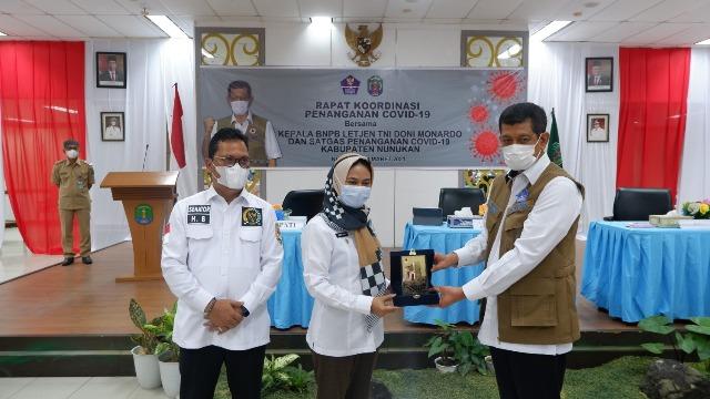 Kepala BNBP Letjen TNI Doni Monardo (kanan) menyerahkan plakat kepada Bupati Nunukan Hj. Asmin Laura Hafid (tengah). Ikut mendampingi Wakil Ketua Komite II DPD RI Hasan Basri. (foto: Tim HB)