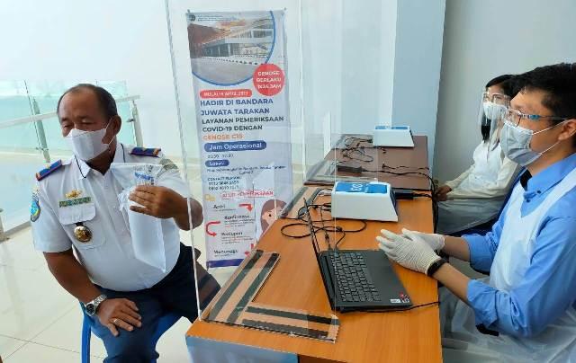 Kepala Bandara Juwata Tarakan Agus Priyanto (kiri) mencoba alat genose. (foto: jendelakaltara.co)